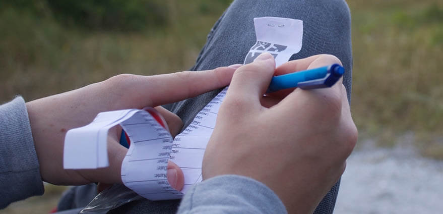 A person in grey sweatpants overlooking a city and grassy field while writing their name in a geocache log book.