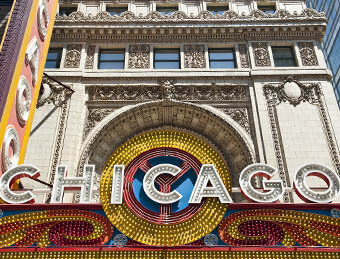 "Classic Chicago architecture with large lighted letters spelling out ""CHICAGO"""